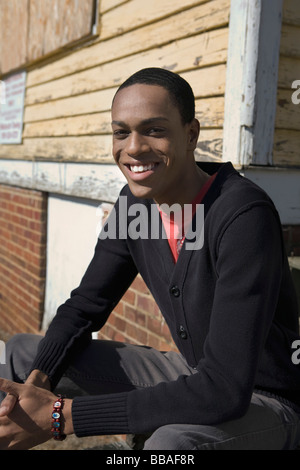 A young man sitting on porch steps - Stock Photo