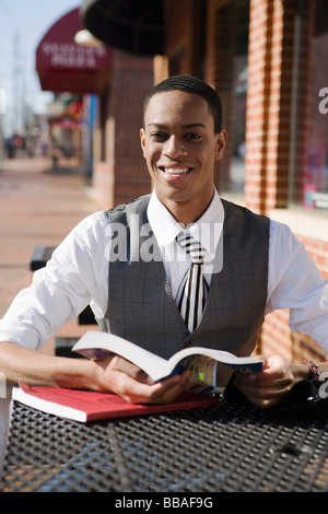 A young man sitting at a pavement cafe and reading books - Stock Photo
