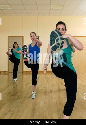women aerobic kick exercise at gym - Stock Photo