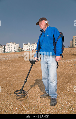 a metal detecting man on brighton beach trying to find money - Stock Photo