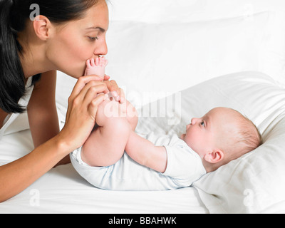 Mother kissing her new-born baby's feet - Stock Photo