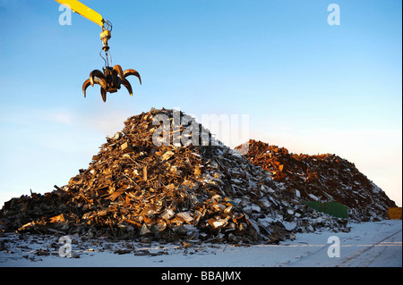 Pile of scrap metal with crane - Stock Photo