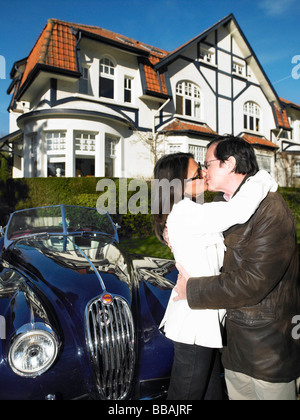 Couple in front of their house and car - Stock Photo