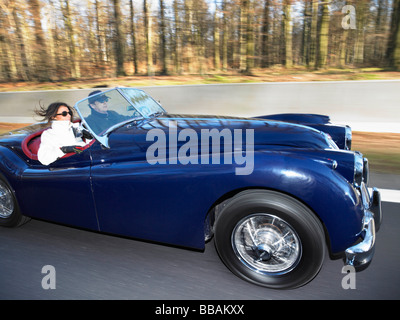 Couple in an old convertible, freeway - Stock Photo