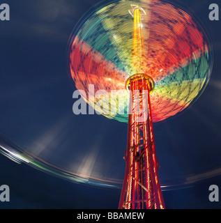 Illuminated chairoplane against dark sky - Stock Photo