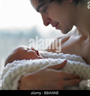 Father holding baby in his arms - Stock Photo