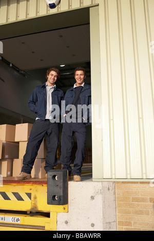 Two workers in warehouse doorway - Stock Photo