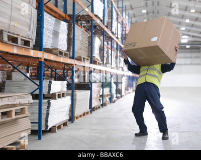 Worker Struggling With Box In Warehouse - Stock Photo