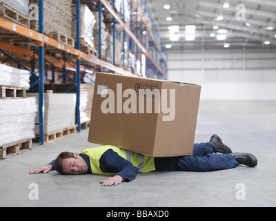 Worker Flattened By Box In Warehouse - Stock Photo