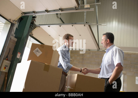 Two businessmen in warehouse - Stock Photo
