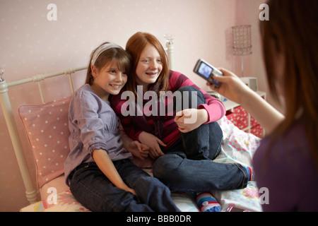 Teenage girl taking photo on phone - Stock Photo