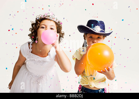 party girls blowing balloons - Stock Photo