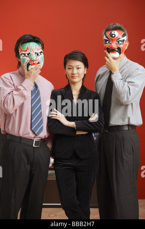 Businesswoman standing between two businessmen with Chinese masks over their faces - Stock Photo