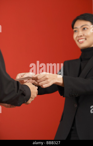 Female executive offering business card to another executive - Stock Photo