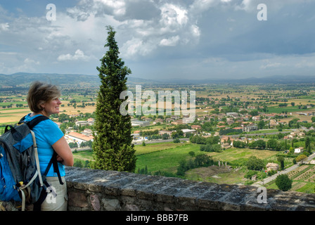One woman tourist with back pack looking out over Umbrian countryside from a viewpoint at Spello with dark clouds - Stock Photo