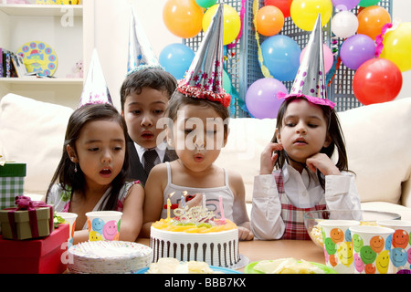 Children celebrating birthday, child blowing candles on cake - Stock Photo