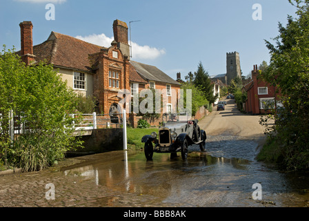Vintage car driven through a ford, Kersey, Suffolk, UK. - Stock Photo