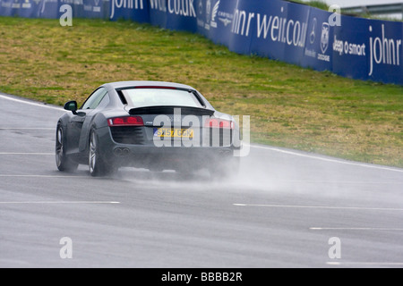 Audi R8 Supercar on wet track - Stock Photo