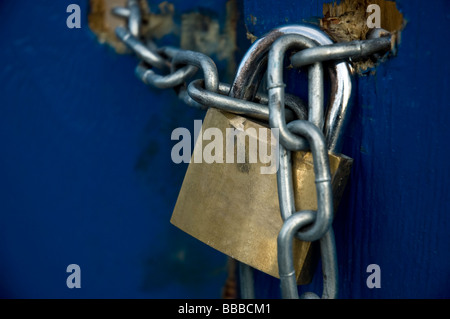 A padlock and chain on a blue wooden door - Stock Photo