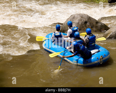 Rafters in inflatable raft by rapid river; - Stock Photo