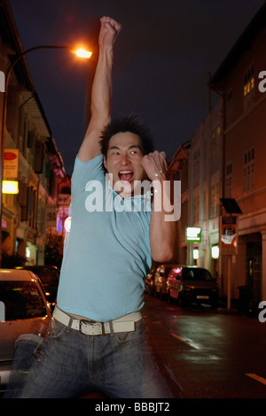 Man standing on street, raising hand, making a fist - Stock Photo