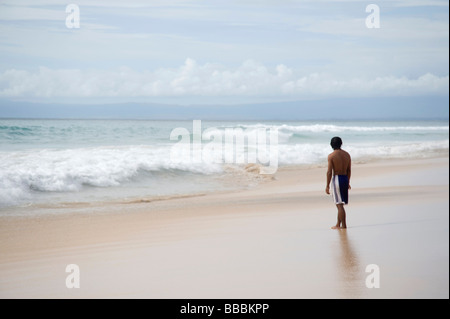 Teenager looking at surf on beach ; - Stock Photo