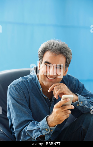 Man with gray hair, hand on chin, holding phone - Stock Photo
