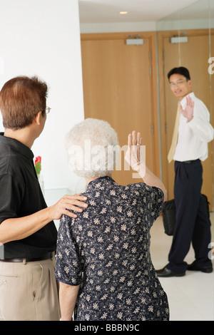 Mature man and woman waving, younger man waving back - Stock Photo