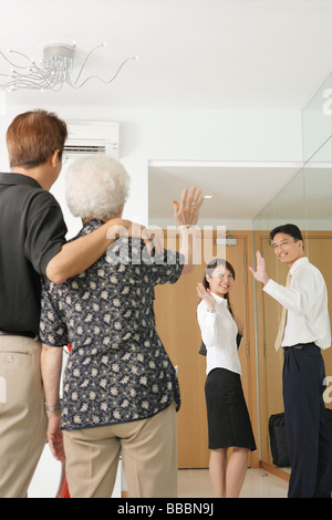 Mature man and woman waving, younger man and woman waving back - Stock Photo