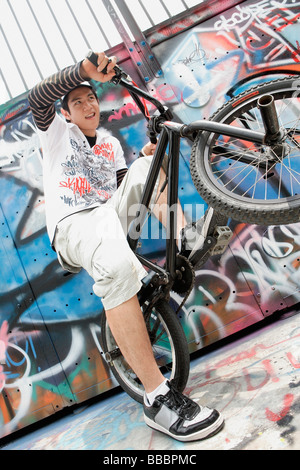 Young man with bicycle next to graffiti wall - Stock Photo