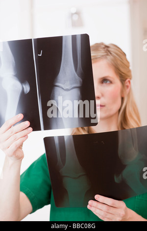 female medic looking at x-ray pictures - Stock Photo