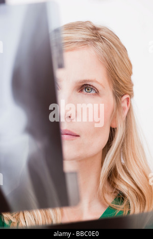 female medic looking at x-ray picture - Stock Photo