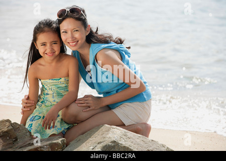 Mother and daughter on beach by rocks - Stock Photo