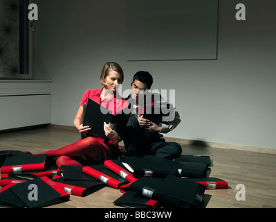 Man and woman playing with binders - Stock Photo