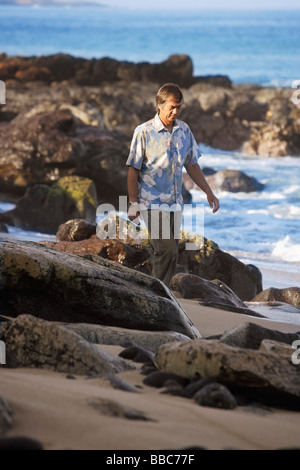 mature man walking along rocky beach - Stock Photo