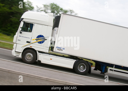 Side view of a white articulated Daf lorry speeding along an English road - Stock Photo