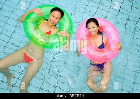 Women in swimming pool, using inflatable rings, looking at camera - Stock Photo
