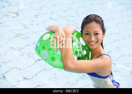 Woman in swimming pool, hugging beach ball - Stock Photo