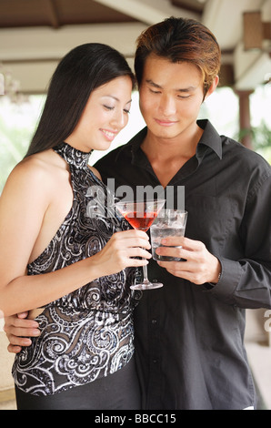 Well dressed couple, holding drinks, toasting - Stock Photo