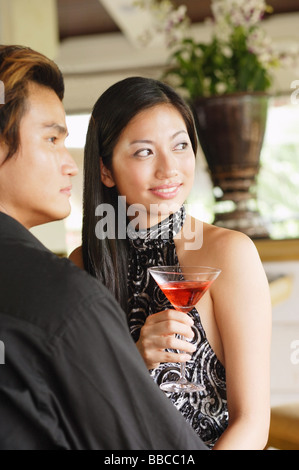 Well dressed couple, looking away, woman holding a drink - Stock Photo