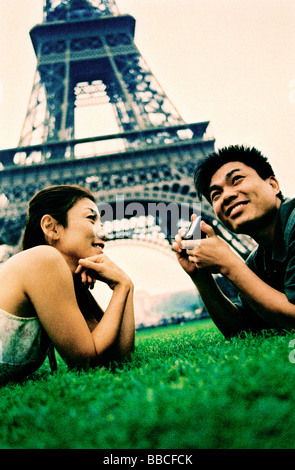 Young couple lying on grass, holding camera, Eiffel Tower in background. (high-grained) - Stock Photo