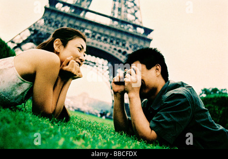 Young couple lying on grass, young woman posing for camera, smiling, Eiffel Tower in background. (high-grained) - Stock Photo