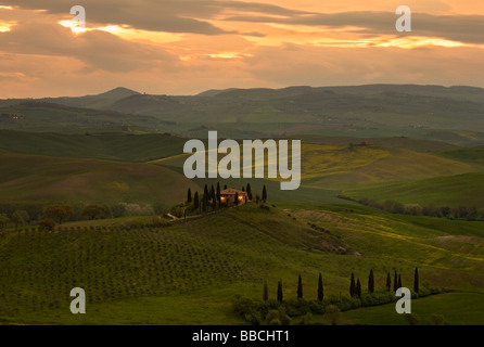 Typical Tuscan villa in early morning light with sun rising over the rolling hills of Val D'orcia, Tuscany, Italy. - Stock Photo