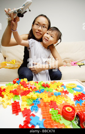 Mother and daughter playing toy airplane - Stock Photo