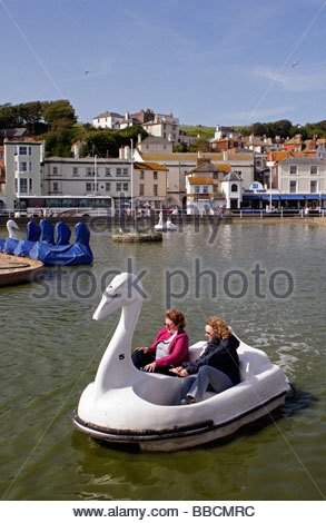 Swan pedalos on the boating pool at May Bank Holiday weekend; Hastings, East Sussex - Stock Photo