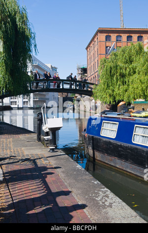 Camden Lock , Camden Stables Market , blue barge moves out of Hampstead Road lock on Regents canal watched by tourists - Stock Photo