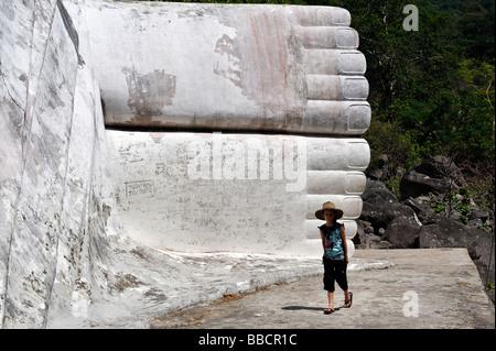 Child near graffiti covered feet of Tuong Phat Nam (white reclining Buddha), Ta Cu mountain, Binh Thuan province, - Stock Photo