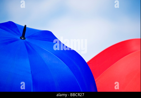 A blue and a red umbrella against the sky - Stock Photo
