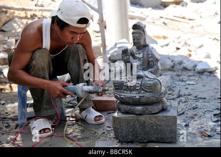 Man carving stone Buddha with electric grinder. Ta Cu mountain, Binh Thuan Province, Vietnam - Stock Photo