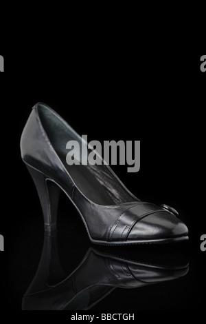 Luxurious designer shoes isolated against black background - Stock Photo